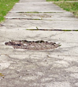 A broken sidewalk like the one in this image can lead to serious injury and an Atlanta premises liability lawyer can help injured victims.