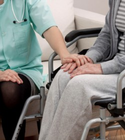 A person in a wheelchair is comforted by medical staff as she considers talking to an Atlanta paralysis lawyer